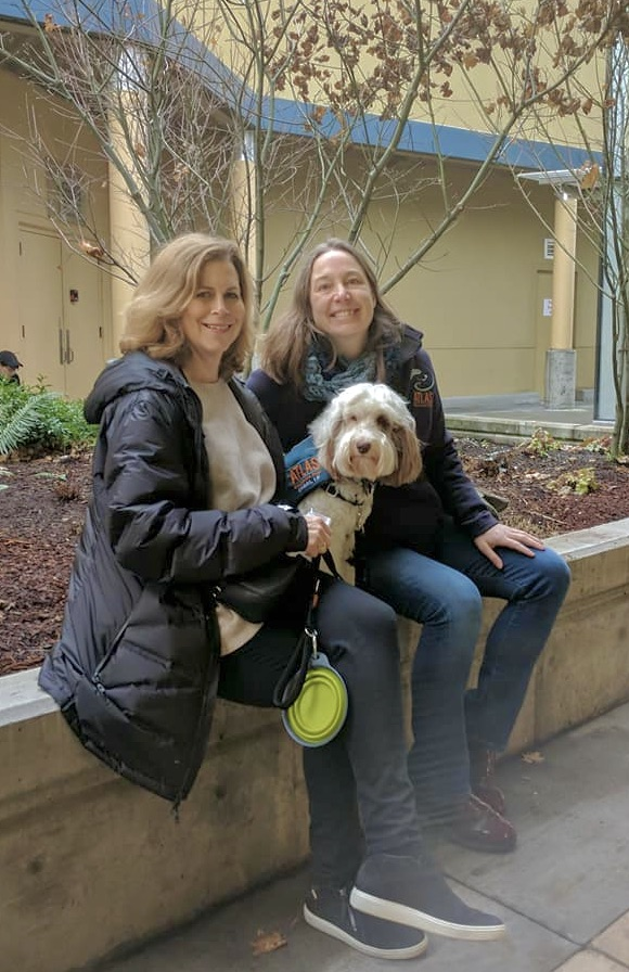 two women (Allison and Jen) are sitting together and smiling. A small fluffy white and brown dog with a navy blue Atlas vest is posing in between the women.